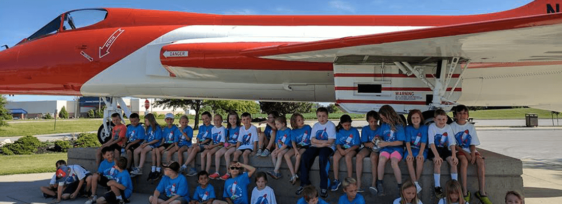 Scout leader resources children posing by a jet